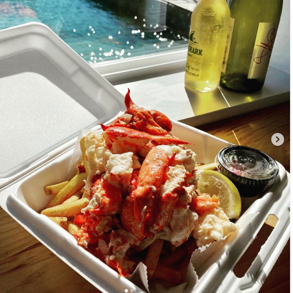 lobster roll plate with fries in a to go box