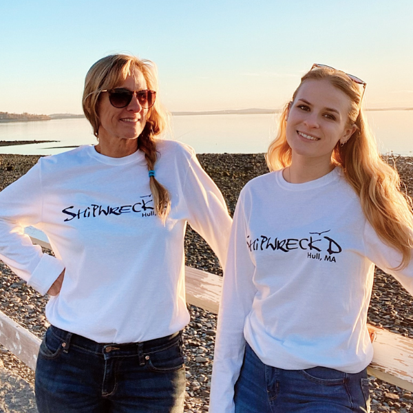 beautiful blonde female models wearing long sleeve white shiprweckd tees in front of the water