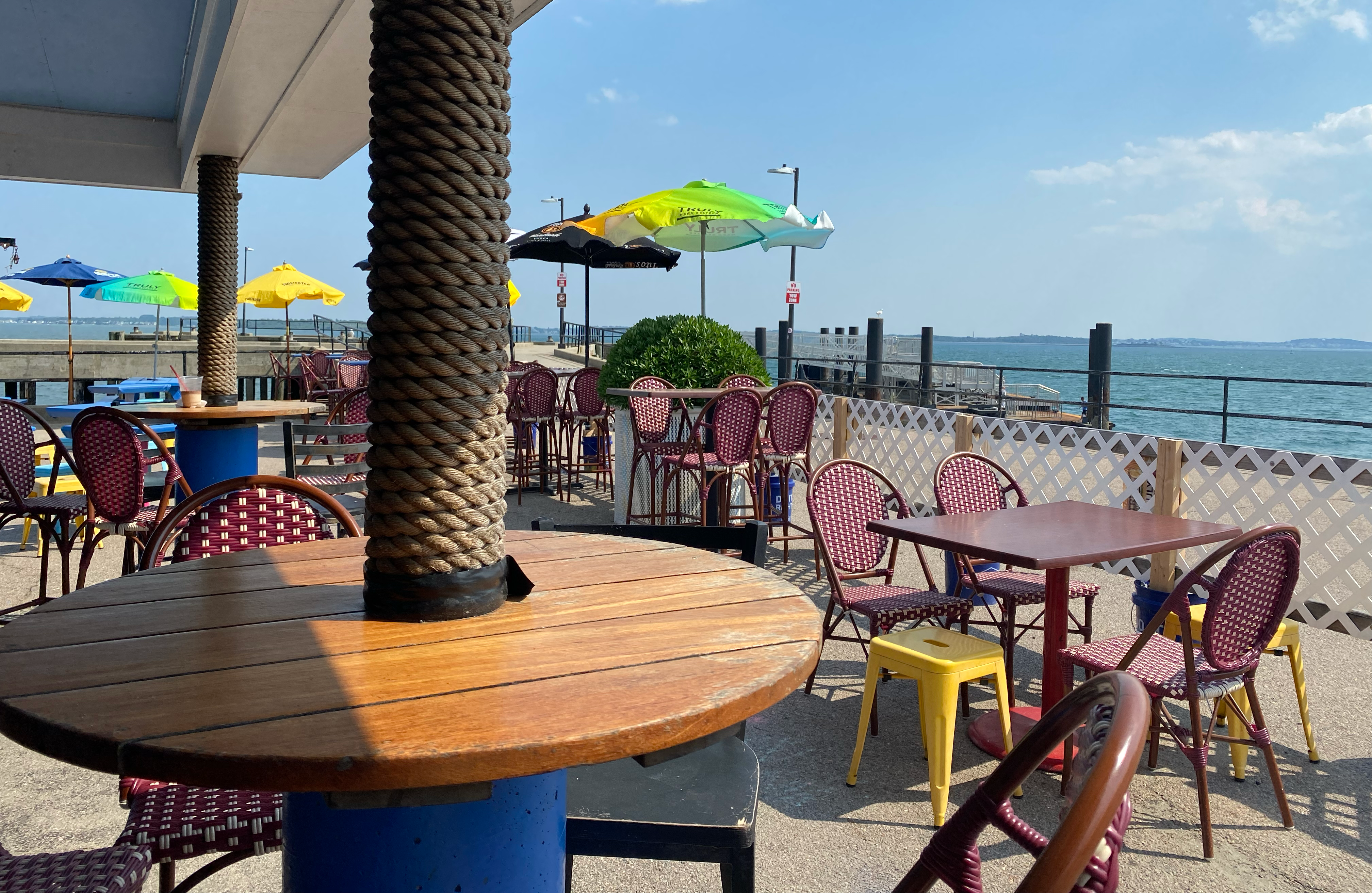 Sunny patio next to pemberton pier with wooden tables and colorful umbrellas